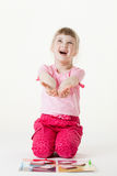 Happy little girl sitting on the floor, reaching out her palms Stock Images