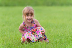 Happy little girl sitting in the grass royalty free stock photography