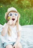 Happy little girl sitting on the green grass with flower dandelion in your hands royalty free stock photos