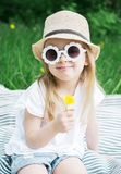 Happy little girl sitting on the green grass with flower dandelion in your hands stock photos