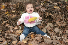 Happy little girl sitting in leaves. Happy little girl sitting in a pile of leaves holding a big yelllow leaf she found Royalty Free Stock Photo