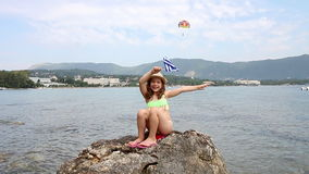 Happy little girl sitting on a rock by the sea stock footage