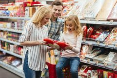 Happy little girl sitting on a shopping cart. And choosing candy with her parents at the supermarket Royalty Free Stock Images