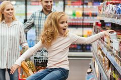 Happy little girl sitting on a shopping cart. And choosing sweets with her parents at the supermarket Stock Image