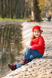Happy little girl sitting on the shore Stock Photo