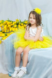 Happy little girl sitting on the sofa near the big bouquet of tu stock photo