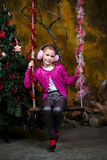 Happy little girl sitting on the swing Stock Image