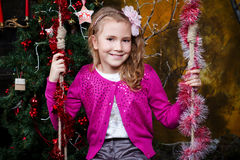 Happy little girl sitting on the swing. Near the a Christmas tree Royalty Free Stock Photography
