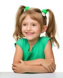 Happy little girl is sitting at the table stock image