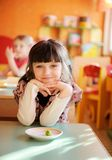 Happy little girl sitting at a table Royalty Free Stock Photos