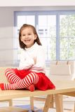 Happy little girl sitting on top of table Stock Image
