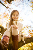Happy little girl sitting on a tree trunk Royalty Free Stock Photography