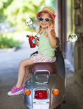 Happy little girl sitting in  a vintage scooter in the street we Stock Images