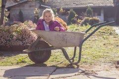 Happy little girl sitting in wheelbarrow Royalty Free Stock Photography
