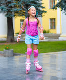 Happy little girl is skating on rollers Stock Images