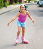 Happy little girl is skating on rollers Stock Photos