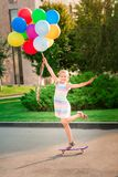 Happy little girl skating on a scateboard with large bunch of helium filled colorful balloons royalty free stock photography