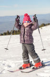 Happy little girl skiing downhill Stock Photos