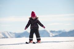 Happy little girl skiing downhill Stock Photo