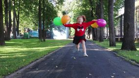 Happy little girl in skirt runs and jumps with balloons. In green summer park stock video footage