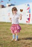 Happy little girl in skirt shows lollipop Stock Photos