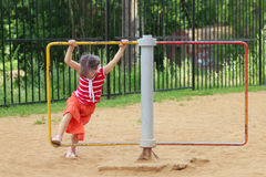 Happy little girl in skirt whirls on roundabout royalty free stock image