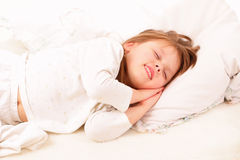 Happy little girl sleeping in bed Royalty Free Stock Images