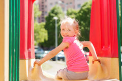 Happy little girl on slide at children playground Stock Image