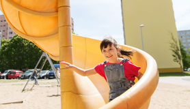 Happy little girl on slide at children playground Royalty Free Stock Photo