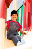 Happy little girl on slide at children playground Stock Photography