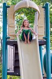 Happy little girl on slide. A smiling little girl in a green dress plays on a playground slide Royalty Free Stock Photography
