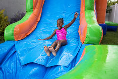 Happy little girl sliding down an inflatable bounce house. Cute smiling little african american girl playing on an inflatable  bounce house outdoors. She is Stock Photos