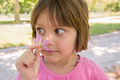 Happy little girl smelling flower Royalty Free Stock Photo