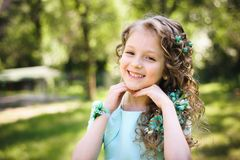 Happy little girl smiling at camera in park royalty free stock photo
