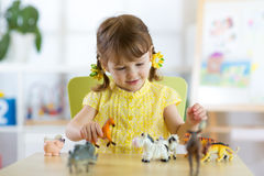 Happy little girl. Smiling child toddler plays animal toys at home or kindergarten. Stock Image