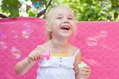 Happy little girl with soap bubbles Stock Images