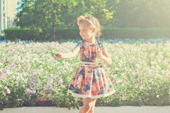 Happy little girl with soap bubbles. Near flower bed Royalty Free Stock Images