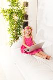Happy little girl with sofa typing Royalty Free Stock Photography