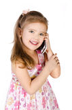 Happy little girl speaking by cell phone. Isolated on white Stock Photo