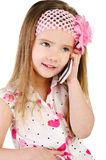 Happy little girl speaking by cell phone isolated. On white Royalty Free Stock Photo