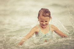 Happy little girl splashing in the sea Stock Photography