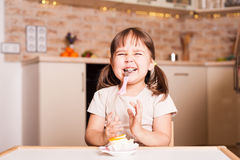 Happy little girl with spoon and cake stock images