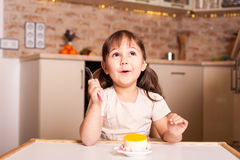 Happy little girl with spoon and lemon cake Stock Photography