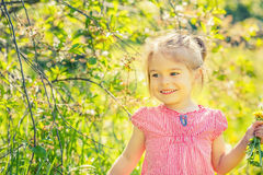 Happy little girl in spring sunny park Stock Photo