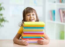 Happy little girl with a stack of books Royalty Free Stock Image