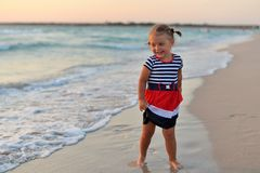 Happy little girl standing barefoot on the wet sand on the beach stock image