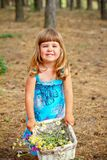 Happy little girl standing with a basket of flowers in the fores Stock Photography