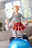 Happy little girl standing on fit ball Royalty Free Stock Photo