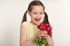 Happy little girl with radish over white background. Happy little girl standing with radish over white background. Healthy food for children concept, copy space Stock Photos