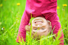 Happy little girl standing upside down on grass in summer park Stock Images